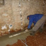 Miro smoothes concrete into place for the floor in Kovaci, Istria