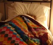 Nicky in bed under duvet