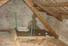 Ensuite bathroom in attic with piping and concrete floor