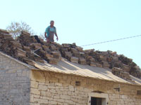 Amir stripping old tiles off the barn in Kovaci, Istria