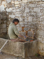 Stonemason sitting in water trough, looking at wall in Kovaci, Istria