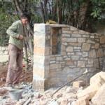 Stonemason crafting Kovaci property's beautiful gateway in Istria
